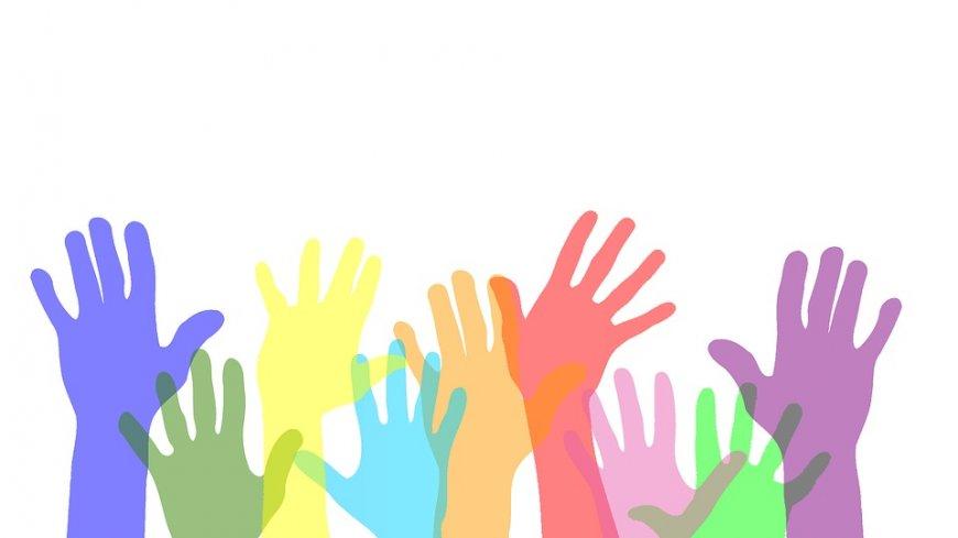 Grafika przedstawia wiele uniesionych, kolorowych rąk.