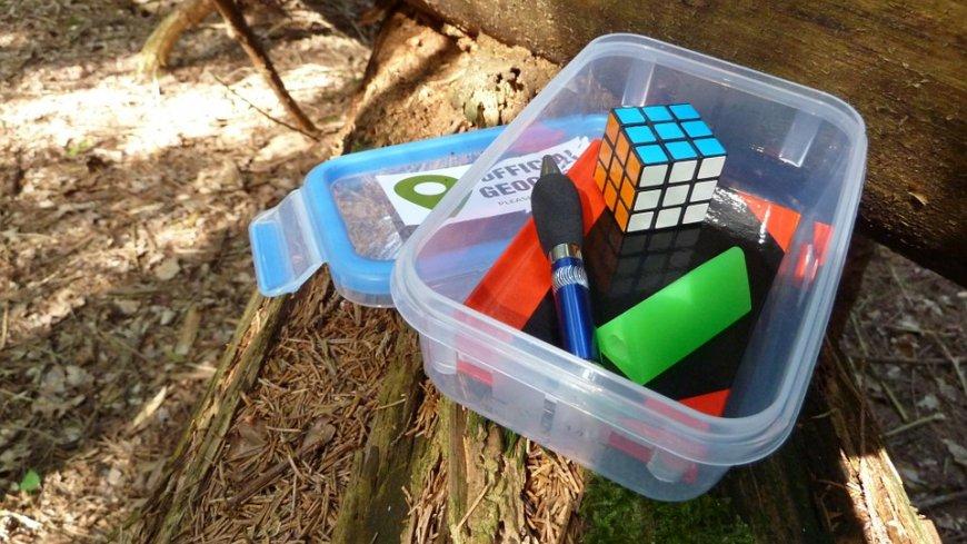 Skrzynka z przedmiotami, w tym kostką Rubika.