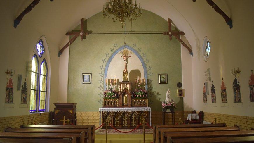 Wnętrze kaplicy - Parafia Rzymskokatolicka p.w. N.M.P. Matki Kościoła w Kostrzynie nad Odrą. Widok na zabytkowy, drewniany, zdobiony ołtarz.