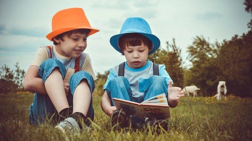 Dwójka chłopców w kapeluszach siedząca na trawie. Przeglądają książkę.
