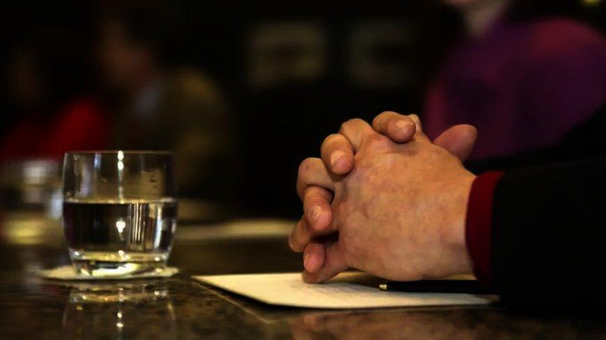 przykładowa grafika przedstawiająca splecione ręce mężczyzny i stojącą przed nim szklankę z przezroczystym płynem
