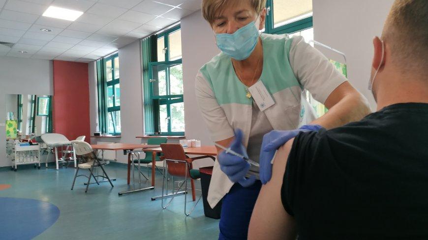 Radna i pielęgniarka Helena Rudaniecka w maseczce i kitlu pielęgniarskim szczepi mężczyznę (widać go tyłem).