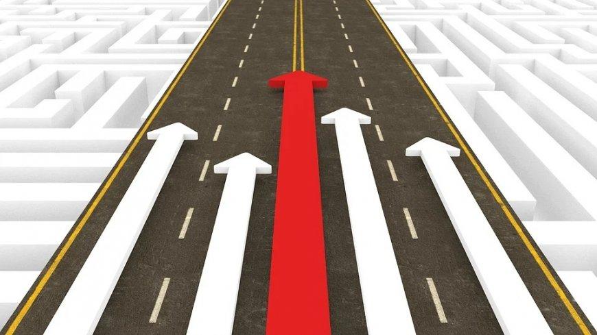 Grafika drogi, przez którą prowadzą białe strzałki oraz jedna, najdłuższa, czerwona na środku.