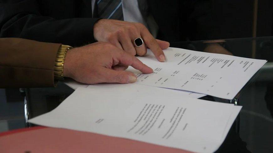 Dwoje ludzi pochylających się nad dokumentami - widoczne jedynie dłonie oraz zadrukowane kartki papieru.