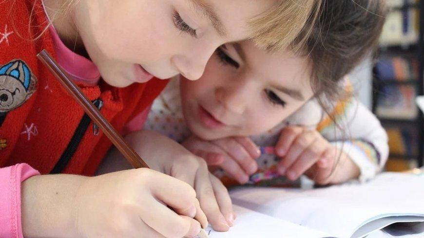 Dwie dziewczynki pochylają się nad zeszytem. Jedna z nich trzyma ołówek.