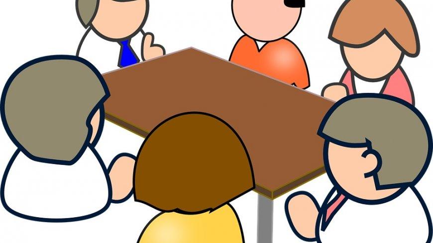 Grafika, kilka osób siedzących przy biurku.