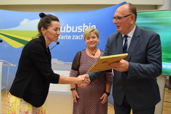 Trzy osoby na zdjęciu, mężczyzna i dwie kobiety. Mężczyzna wręcza nagrodę pani Elżbiecie Ratajczak.